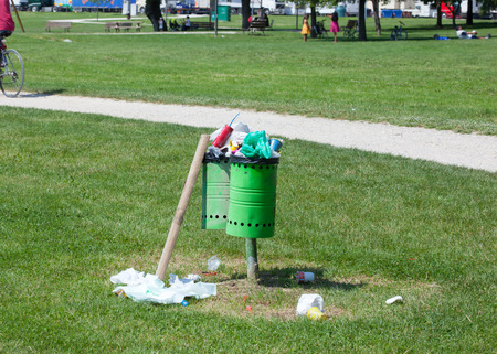 wastes: Trash bin ful with wastes on the groundl in an outdoor park. Editorial