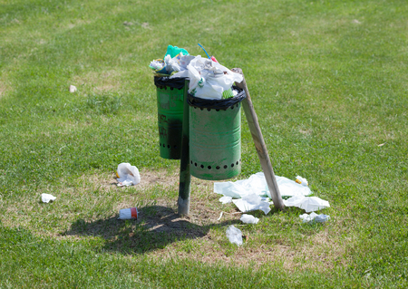 ful: Trash bin ful with wastes on the groundl in an outdoor park. Stock Photo