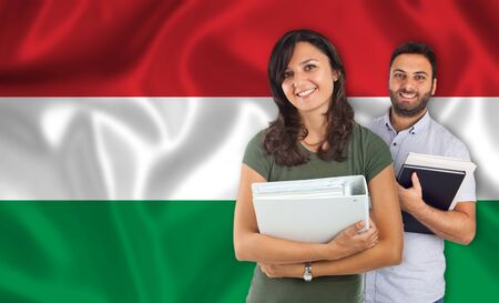 parlance: Couple of young students with books over Hungarian flag