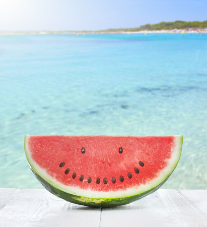 Slice of watermelon with seeds that make a smiling face on the beach