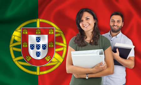 internships: Couple of young students with books over Portuguese flag Stock Photo