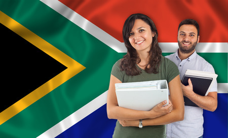 interpreter: Couple of young students with books over South Africa flag Stock Photo