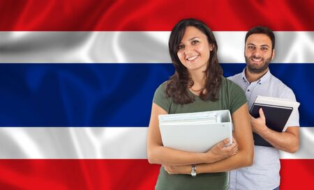 parlance: Couple of young students with books over Thai flag