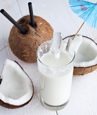dring: Spalsh drink with milk and coconut on white wooden table. Stock Photo