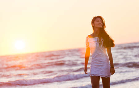 vestido blanco: Beautiful young teenager with a white dress on the beach at sunset.