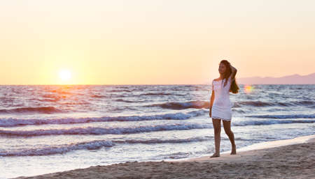 vestido blanco: Adolescente joven hermosa con un vestido blanco en la playa al atardecer. Foto de archivo
