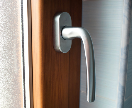 Close up of window handle with faux wood frame