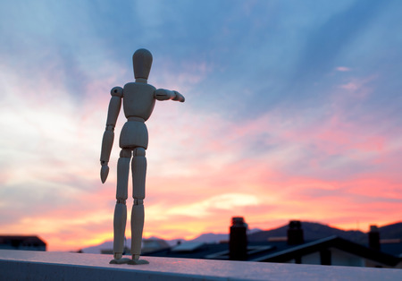 equipoise: Wooden dummy pointing with his finger towards the horizon at sunset
