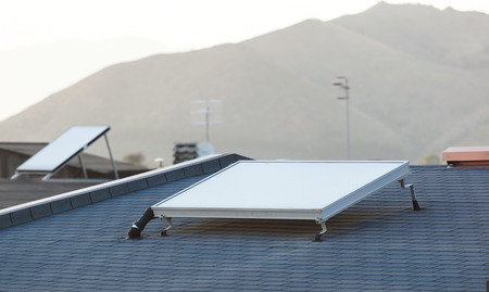 voltaic: Solar panel for water heating system on the roof.