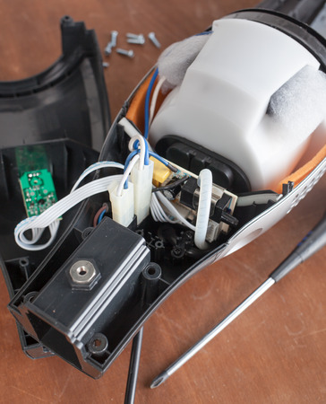 Vacuum cleaner disassembled for repair malfunctioning on work table