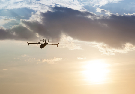 backlite: Silhouette of an airplane at sunset in the clouds Stock Photo