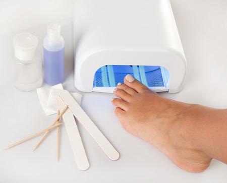 pedicura: Pies de pedicura y tratamiento de uñas con productos cosméticos y lámpara UV
