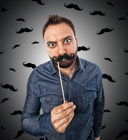 mustaches: Young man with photo booth shaped mustache and background with small mustaches Stock Photo