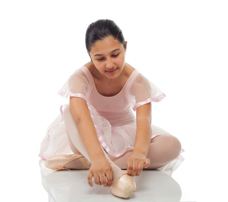 long toes: Young dancer while tying his shoes for dancing on white background.
