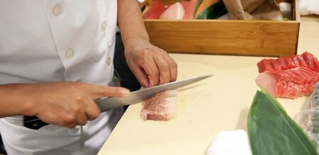 chelsea market: Hand was sliced fish to make sushi in chelsea market, New York. Stock Photo