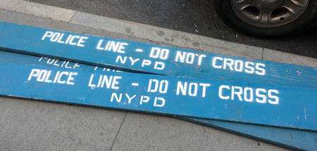 wrongdoing: Police Line Do Not Cross. A Police line do not cross police department crime scene sign on the sidewalk in New York City.