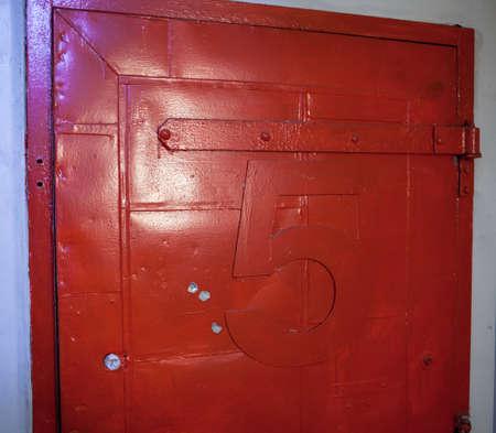 fire door: Vintage fire door painted red with number five Stock Photo