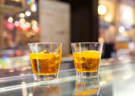 spritz: Two glasses of spritz aperitif cocktail with orange slices.
