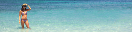 landscape format: Beautiful young woman in bikini relaxing in water, Es Trenc beach, landscape format.