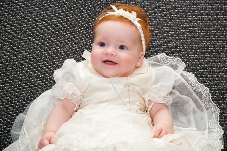baptismal: Portrait of a baby in baptismal clothing sitting on sofa