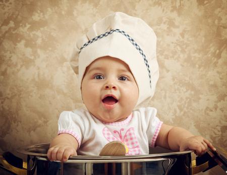 Chef bébé mignon dans un énorme chaudron sur la table en bois Banque d'images