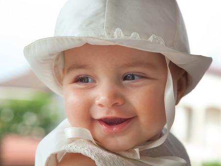 Portret van een kind een paar maanden met witte jurk en hoed op de dag van haar doop.