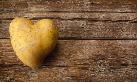health symbols metaphors: Heart shaped potato on dark wooden table.