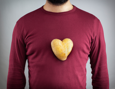 people isolated: Young man with a potato shaped heart on his chest.