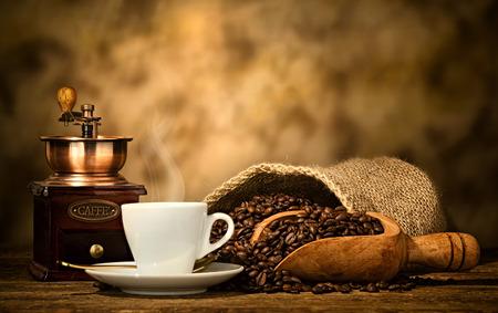 Tazza di caffè espresso, chicchi di caffè e vecchio macinino da caffè sul tavolo di legno.