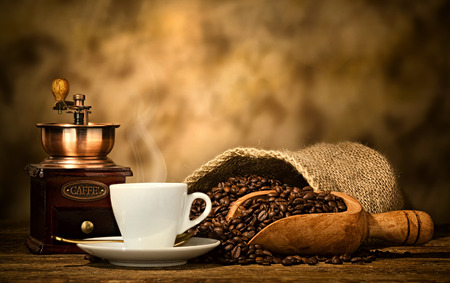 wooden spoon: Cup of espresso coffee, coffee beans and old coffee grinder on the wooden table.