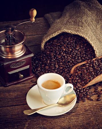 tazas de cafe: Taza de café espresso, granos de café y molinillo de café de edad en la mesa de madera.