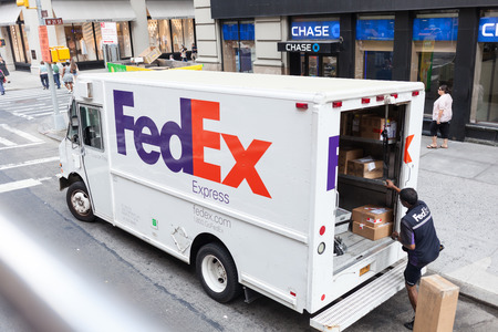 NEW YORK CITY , USA - JULY 07, 2015: FedEx Express truck in midtown Manhattan. FedEx is one of the leading package delivery services offering many different delivery options.