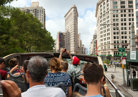 flatiron: NEW YORK CITY , USA - JULY 07, 2015: Flatiron building facade with tourists in bus. Completed on 1902, it is considered to be one of the first skyscrapers ever built.