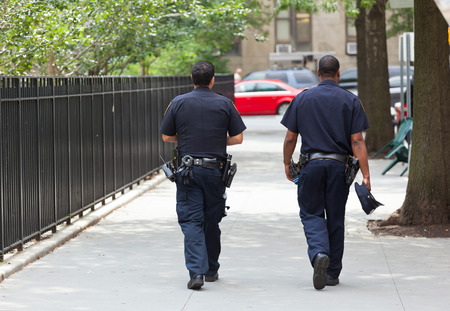NEW YORK CITY , USA - JULY 07, 2015: Two police officers from the back in the center of Manhattan.. NYPD, established in 1845, is the largest municipal police force in the United States. 報道画像