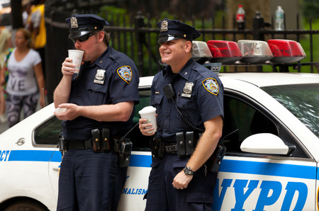 NEW YORK CITY , USA - JULY 07, 2015: Two police officers while drinking a cup of coffee. NYPD, established in 1845, is the largest municipal police force in the United States.