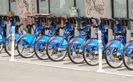 hundreds and thousands: NEW YORK CITY, NY, USA - JULY 07, 2015: Row of Citi Bikes waiting to be rented in Manhattan. The Citi Bike system features thousands of bikes at hundreds of stations around New York.