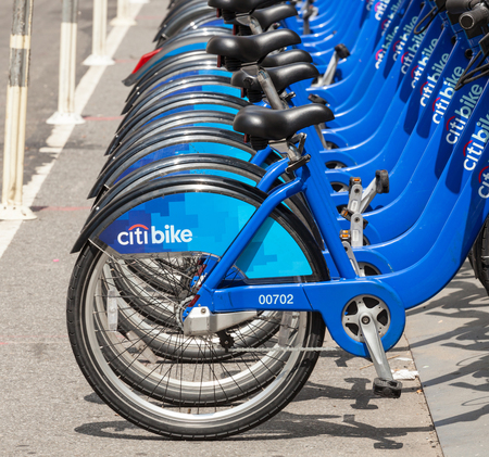 rented: NEW YORK CITY, NY, USA - JULY 07, 2015: Row of Citi Bikes waiting to be rented in Manhattan. The Citi Bike system features thousands of bikes at hundreds of stations around New York.