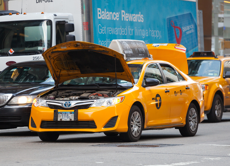 taxicabs: NEW YORK CITY, NY, USA - JULY 07, 2015: Yellow cab stopped in traffic due to the broken engine in Manhattan, NYC. The taxicabs of New York City are widely recognized icons of the city.