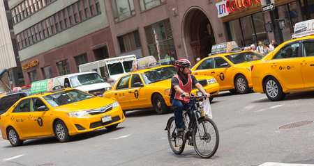 taxicabs: NEW YORK CITY, NY, USA - JULY 07, 2015: Cyclist in traffic between the yellow cabs in Manhattan, NYC. The taxicabs of New York City are widely recognized icons of the city.