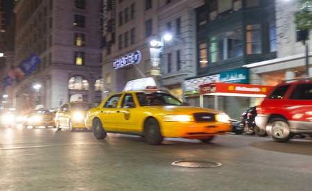 taxicabs: NEW YORK CITY, NY, USA - JULY 07, 2015: Yellow cab in motion blur at night in Manhattan, NYC. The taxicabs of New York City are widely recognized icons of the city.