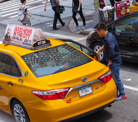 taxicabs: NEW YORK CITY, NY, USA - JULY 07, 2015: Asian tourist takes the yellow cab in Manhattan, NYC. The taxicabs of New York City are widely recognized icons of the city.