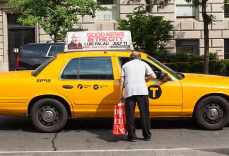 taxicabs: NEW YORK CITY, NY, USA - JULY 07, 2015: A man asks for information a taxi driver in Manhattan. The taxicabs of New York City are widely recognized icons of the city. Editorial