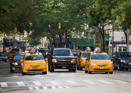 taxicabs: NEW YORK CITY, NY, USA - JULY 07, 2015: Yellow cabs in Manhattan in a rainy day. The taxicabs of New York City are widely recognized icons of the city.
