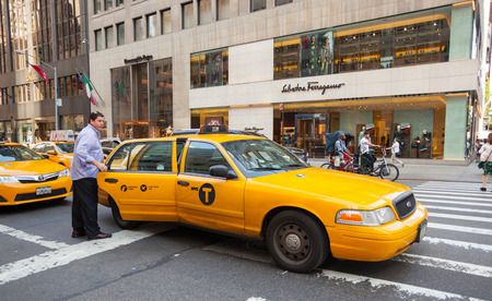 taxicabs: NEW YORK CITY, NY, USA - JULY 07, 2015: Tourist takes the yellow cab in Manhattan near the stores Salvatore Ferragamo.  The taxicabs of New York City are widely recognized icons of the city. Editorial