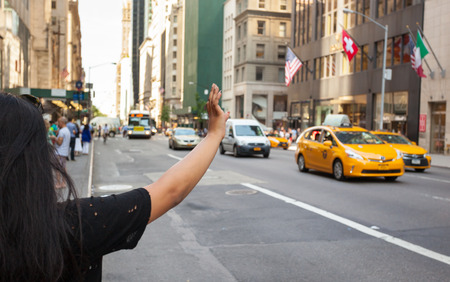 taxicabs: NEW YORK CITY, NY, USA - JULY 07, 2015: Tourist call a yellow cab in Manhattan with typical gesture with arm up. The taxicabs of New York City are widely recognized icons of the city.