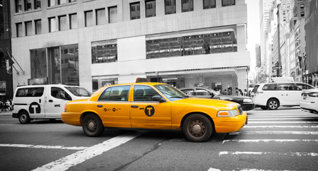 recognized: Yellow cab in Manhattan with black and white background. The taxicabs of New York City are widely recognized icons of the city.