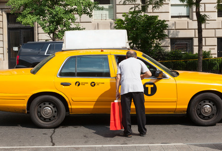 recognized: A man asks for information a taxi driver in Manhattan. The taxicabs of New York City are widely recognized icons of the city.