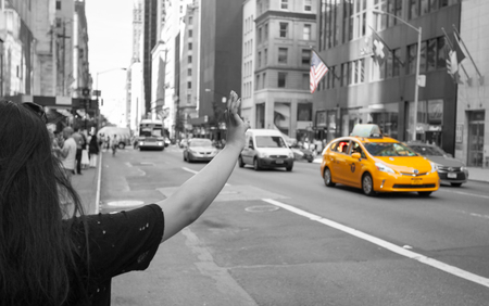 taxicabs: Tourist call a yellow cab in Manhattan with typical gesture with arm up. The taxicabs of New York City are widely recognized icons of the city.
