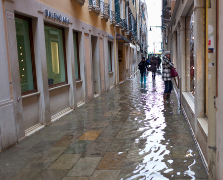 inflow: Venice, Italy - February 01, 2015: Alley in Venice with high tide. Its a phenomenon which occurs in winter time. This can cause of a large inflow of water into the Venetian Lagoon.