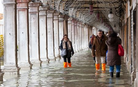 occurs: Venice, Italy - February 01, 2015: Tourists in San Marco square with high tide. Its a phenomenon which occurs in winter time. This can cause of a large inflow of water into the Venetian Lagoon.